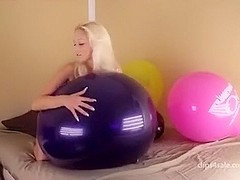 Blond girl bounce some big balloons
