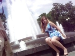 Young girl in a blue dress sitting at the fountain
