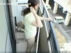 Asian girl masturbates on the balcony of her apartment