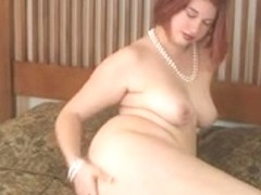 Corpulent redhead undresses and play