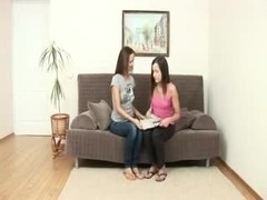 Sexy brunette lesbians playing with a strapon dildo