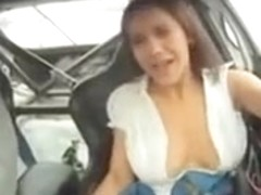 Bombshell's boobs pop out in a race car