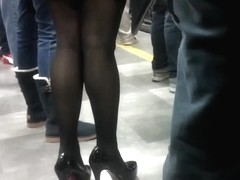 Black stilettos waiting for the train