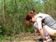 Redhead chick piss in the forest