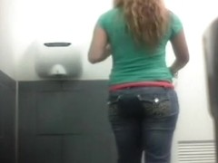 Blonde in jeans pants peeing in toilet
